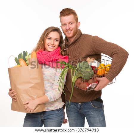 Young couple with grocery shopping bags isolated on white background. Happy couple with fruits and vegetables. - stock photo