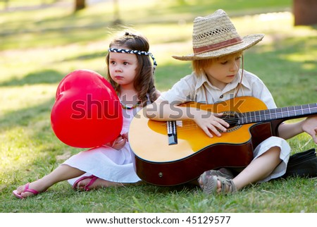 Young couple with guitar on grass in park - stock photo