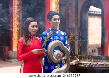 Young couple with incense sticks standing in front of urn in the temple - stock photo