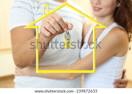 Young couple with keys surrounded by form of house - stock photo