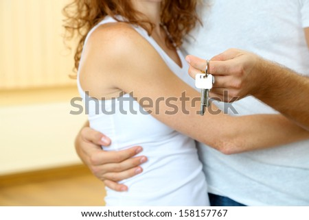 Young couple with keys to your new home close-up - stock photo