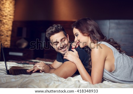 Young couple with laptop lying in bed, wi-fi technology - stock photo