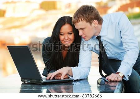Young couple with laptop on the embankment. - stock photo