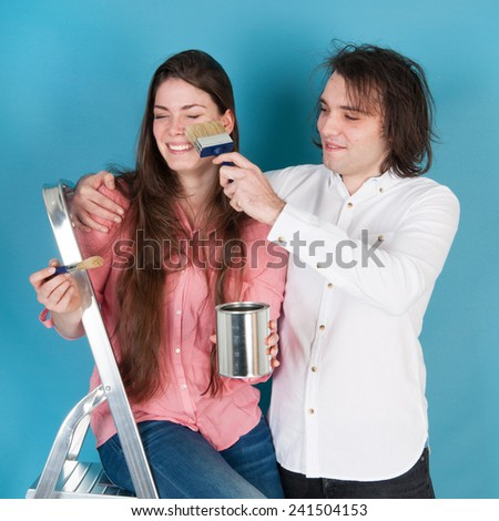 Young couple with paint and brushes in interior - stock photo