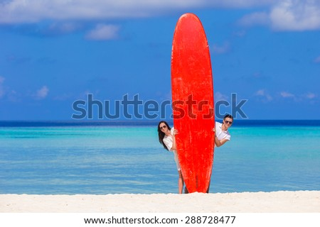 Young couple with red surfboard on white beach - stock photo