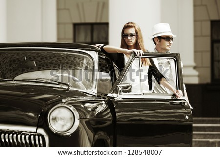 Young couple with retro car on a city street - stock photo
