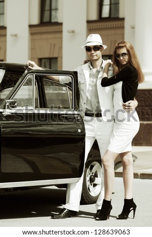 Young couple with retro car on the city street - stock photo