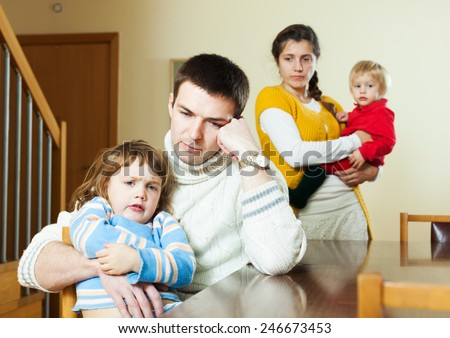 Young couple with small children in quarrel - stock photo