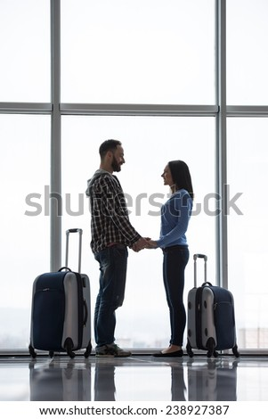 Young couple with suitcases near the panoramic window while waiting for flight. Side view. - stock photo