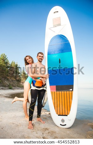 Young couple with sup board on the beach. Concept of harmony with the nature, free and healthy living, freelance, remote business. - stock photo