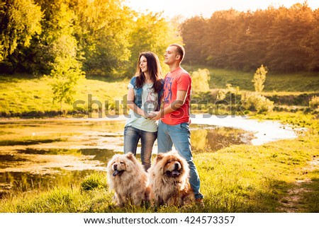 Young couple with the dogs in the park. Sunset - stock photo