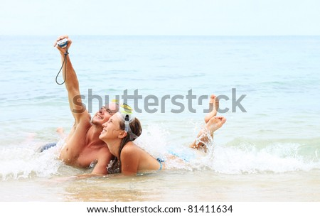 Young couple with the masks making photo of themselves in the sea - stock photo