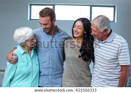 Young couple with their grandparents in living room - stock photo