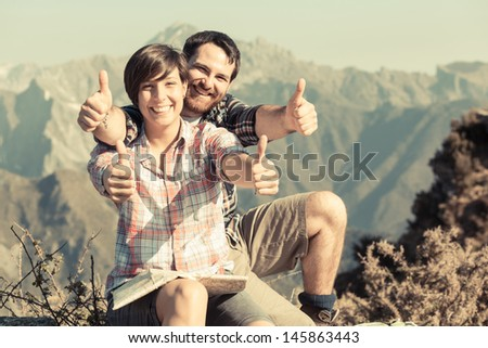 Young Couple with Thumbs Up at Top of Mountain - stock photo