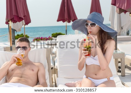 Young Couple with Tropical Drinks Relaxing on Lounge Chairs on Sunny Deck of Oceanfront Luxury Beach Resort - stock photo