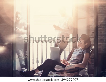 Young couple work together. Photo woman and bearded man working with new freelance project in modern building. Using contemporary notebook, smartphone. Horizontal, film effect. Blurred background - stock photo