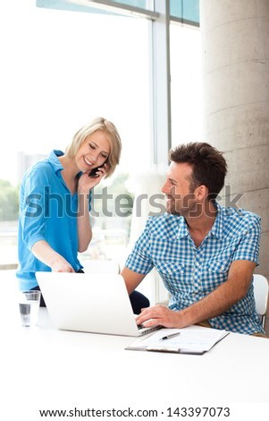 Young couple working together on a laptop in the office. Teamwork concepts. - stock photo