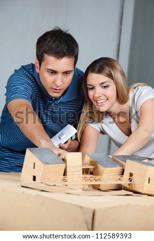 Young couple working together on their future model house - stock photo