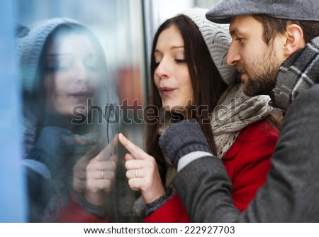 Young couple writing on steamed up window in winter weather - stock photo