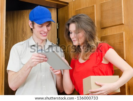 Young courier deliver package to pretty woman - stock photo