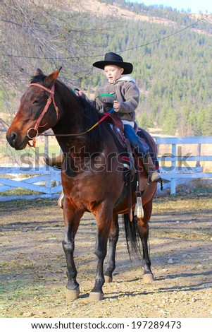Young cowboy riding his horse on the farm - stock photo