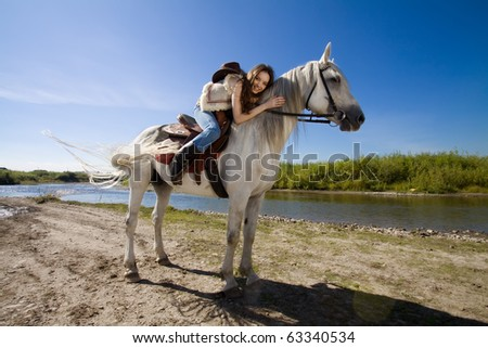 young cowgirl on white horse at the rural river - stock photo