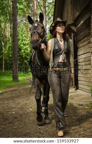 Young cowgirl with brown horse on the ranch - stock photo