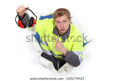 young craftsman pointing at earmuffs - stock photo