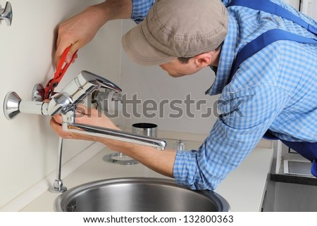 Young craftsman repairing Tap in a kitchen - stock photo