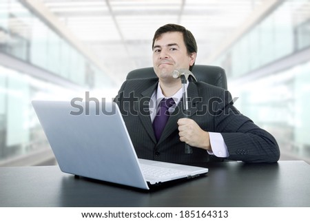 young crazy businessman with a hammer smashing a laptop, at the office - stock photo