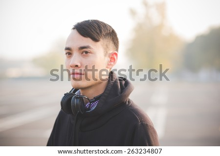 young crazy funny asian man in town outdoor lifestyle - stock photo