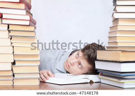 Young crazy tired discontent student between books - stock photo