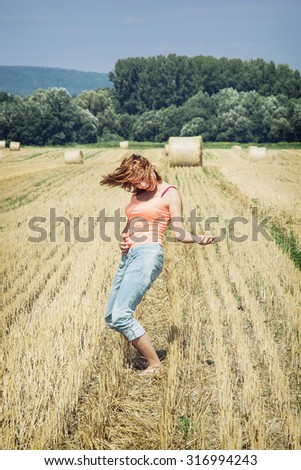 Young crazy woman imitates guitar play at the field. Country concept. - stock photo