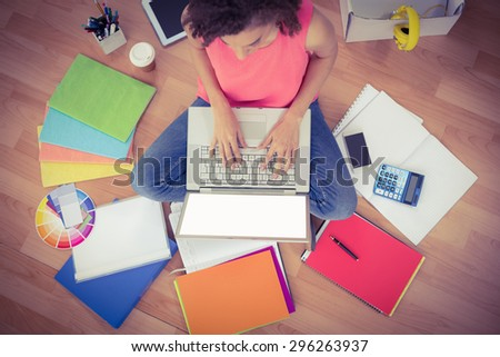 Young creative businesswoman working on laptop on the ground - stock photo