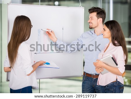 Young creative office workers analyzing marketing results on flip chart. - stock photo