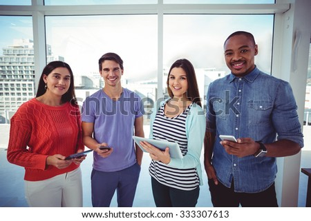 Young creative team looking at phones and tablets in casual office - stock photo