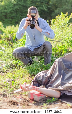 Young criminalist takes picture of crime scene - stock photo