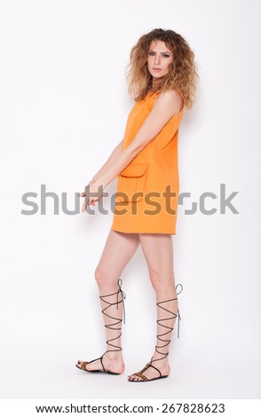 young curly woman smiling and posing in a orange skirt, on white background - stock photo