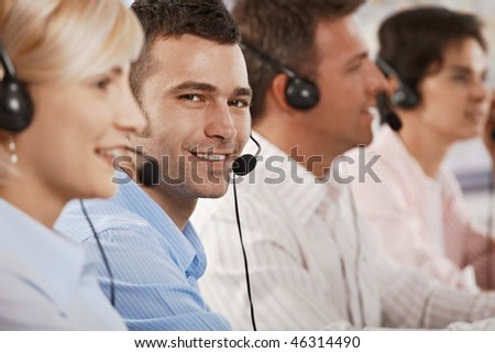 Young customer service operator wearing headset, looking at camera, smiling. - stock photo