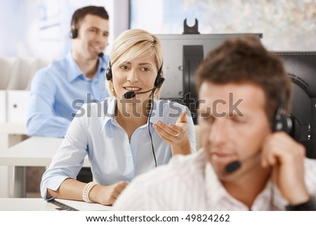 Young customer service operators working in office, smiling. - stock photo