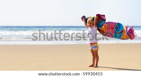 Young cute blonde child on vacation is holding a sarong in the wind - stock photo