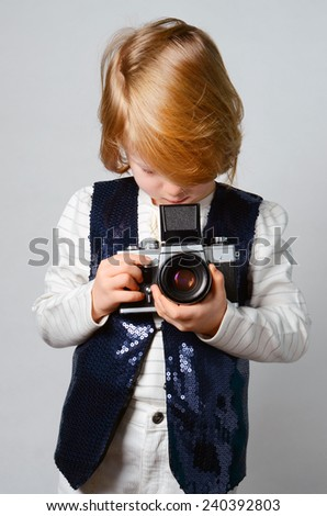 Young, cute, blonde girl holding vintage camera in the studio - stock photo