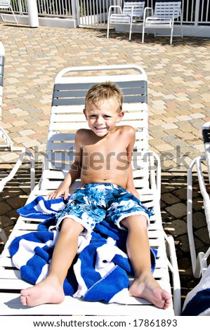 Young cute boy laying on a lounge chair getting a sun tan. - stock photo