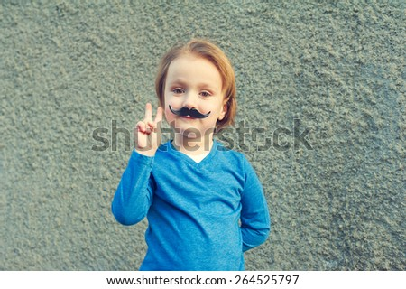 Young cute caucasian boy of 4 years old with a fake Italian moustache making a peace sign with his right hand standing in front of an old grey stone wall - stock photo
