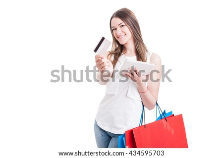 Young cute customer doing using tablet for online shopping and debit card for paying isolated on white with advertising area - stock photo