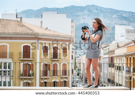 Young cute female tourist with a photo camera in her hands - stock photo