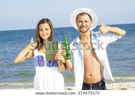 Young cute girl and handsome man on the beach with a book and a bottle of beer in his hands. Like beer and book. - stock photo