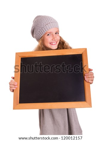 Young cute girl holds a small blackboard and is smiling into the camera - stock photo