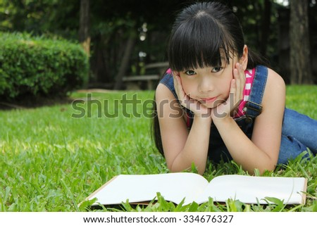 Young cute girl reading in the park - stock photo