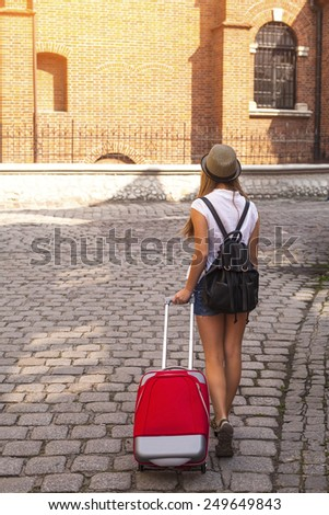 Young cute girl travels through the cities of old Europe. An abstract girl - rear view, pavement, red suitcase. - stock photo